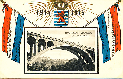 Above a black and white photograph of the Adolf Bridge (span: 84 meters)is the shield of Luxemburg, a red lion rampant on a background of blue and white horizontal stripes. Above the shield is a radiating crown and the years 1914 and 1915. The flag of Luxemburg - three horizontal bars of red, white, blue - is on either side.