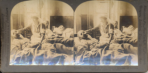 Stereo card view of wounded Belgian soldiers in an Antwerp hospital attended by a Red Cross nurse. The nurse attends to a severely wounded soldier whose head, face, and hands are swathed in bandages.