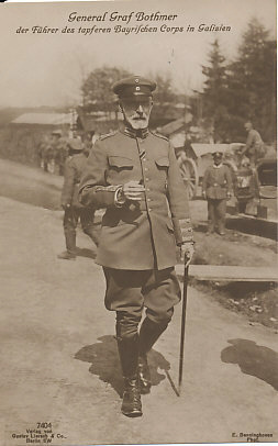 Full-length portrait photograph of General Felix Graf von Bothmer walking with a walking stick in his left hand, and a cigar in his right. Troops in the background. Photograph by E. Benninghoven, published by Gustav Lierach & Co., Berlin SW.
