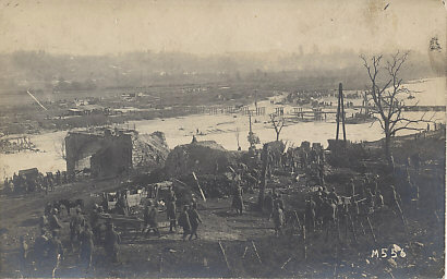 'The first tread-way bridge built across the Isonzo river' is in the background, a destroyed bridge in the foreground, and another under construction. Austrian and German soldiers watch POWs — most likely Italian — draw carts, and cut and trim logs. 'In the background our trenches', and dozens of horse-drawn wagons waiting to cross the tread-way bridge. (The quotations are from a handwritten note on the reverse; translation Thomas Faust.)