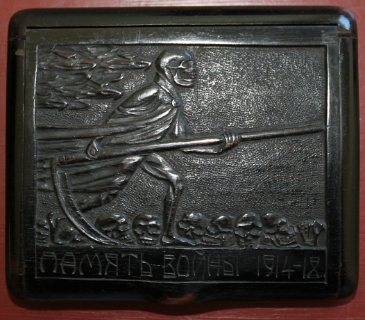 Wooden cigarette box carved by Г. САВИНСКИ (?; G. Savinskiy), a Russian POW. The Grim Reaper strides across a field of skulls on the cover. The base includes an intricate carving of the years of war years, '1914' and, turning it 90 degrees, '1918.'