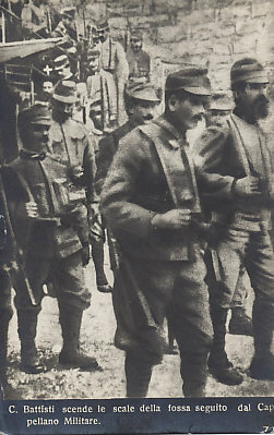 Cesare Battisti, in the background, indicated by a white cross over his head, being marched by Austro-Hungarian soldiers to his execution by garrotting, July 12, 1916. Battisti struggled for Italia irredenta, unredeemed Italy, Austro-Hungarian territory populated largely by ethnic Italians. The picture is from a series of photographs released by the Austrians as postcards.