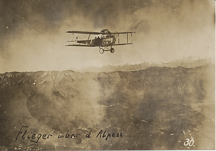 Hansa-Brandenburg C.I two-seater armed reconnaissance plane flying over the Alps. The distinctive radiator at the edge of the upper wing and rear-mounted machine gun are clearly visible. Of German origin, the plane was used extensively by the Austro-Hungarian forces.
