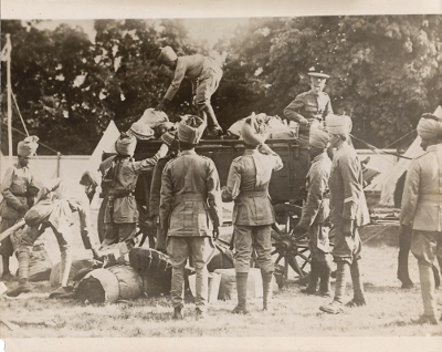 India soldiers unload a wagon. The caption on the back refers to the soldiers helping the Allies by 'unloading their baggage,' but Indian soldiers fought on their own.