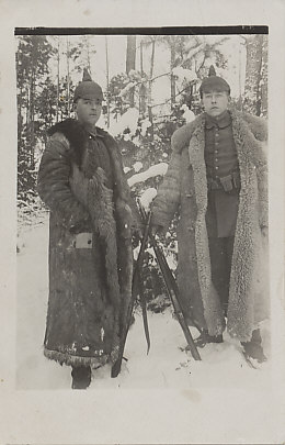 "Photograph of two German soldiers in spiked helmets and fur coats, standing in snow woods, holding their rifles with bare hands, dated January 24, 1918. A short translation from the reverse: "". . . The Russians are already gone. They are right. We should do the same . . . "" (translation, Thomas Faust)."