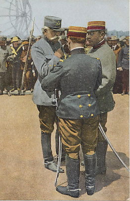 French General Maurice Sarrail decorating officers near the frame of German Zeppelin shot down on May 5, 1916 by naval gunners in view of the citizens of Salonica, Greece. General Sarrail commanded the Allied troops at the front that included French, British, Serbian, Russian, and Italian troops, as well as a battalion of Montenegrin soldiers. The Zeppelin's frame is in the background, and civilians are among the observers of the ceremony.