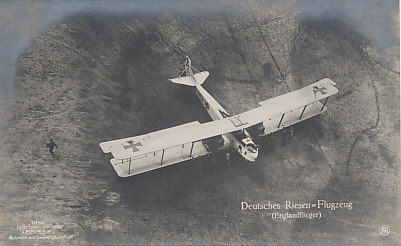 A large German bomber, capable of bombing England. The plane is powered by two engines, and holds a crew of three with a pilot and front and rear gunners. The plane is likely a Gotha bomber, originally built by Gothaer Waggonfabrik, then built under license by Siemens-Schukert Werke and Luft-Verkehrs-Gesellschaft (LVG). Note the ground crew pushing on the lower wing and the men holding the tail up as the plane is moved backwards. Sanke postcard number 1040.
