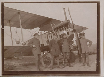 German pilot Kleim with his observer, ground crew, and LVG bi-plane. Kleim is marked with an 'x' above his head, standing, outer coat open, hands on his hips. The plane may be an early model C.II introduced in late 1915. It has wire wheels of the earlier B.I, and what may be an early exhaust pipe. The more typical C.II positions the exhaust at the midpoint of the engine.