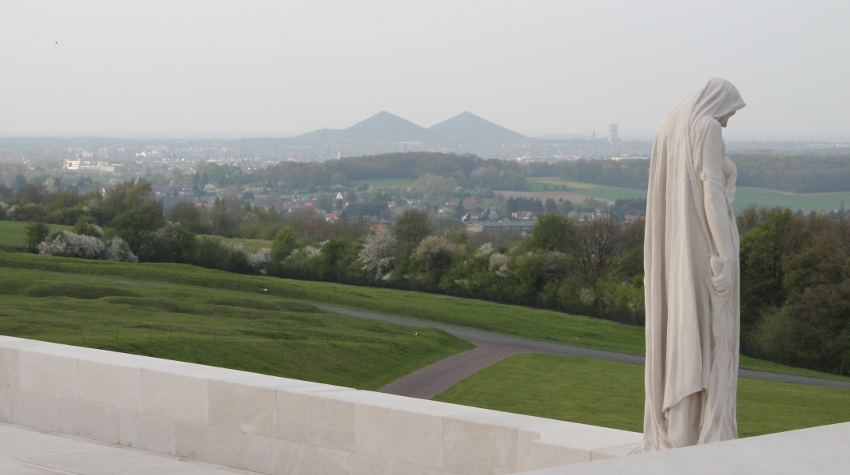 Detail from the Canadian Memorial at Vimy Ridge: the figure of Canada Bereft, or Mother Canada, looking down at a casket below her, mourns her dead. In the distance are the slag heaps of Lens and the Douai Plain.