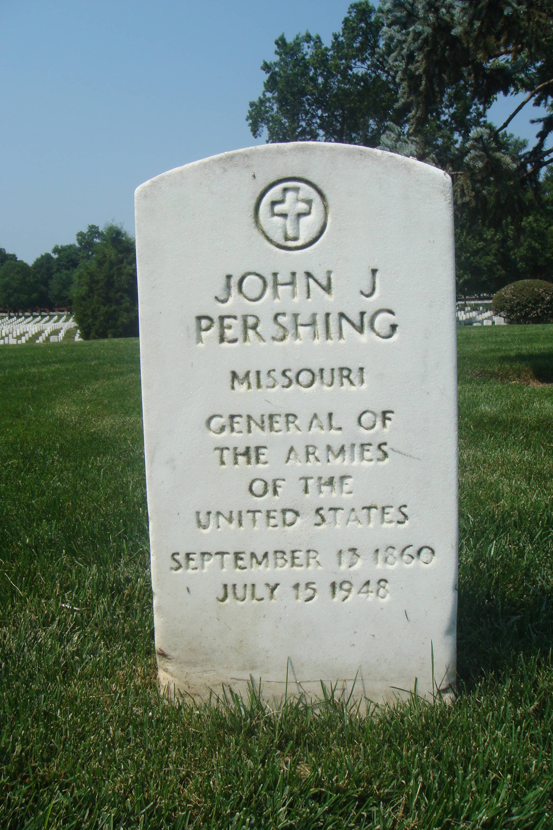 The gravestone of General John J. Pershing in Arlington National Cemetery. Throughout the cemetary, the headstones are uniform. Pershing is buried in a clearing at the top of a rise, with his son nearby, and men he led on the slopes around him.