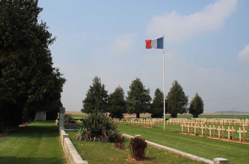 The French flag, ossuaries, and headstones, Biaches Military Cemetery on the Somme.